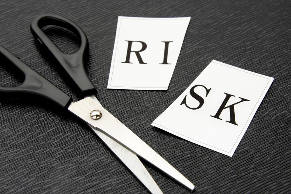 ハサミでリスクと書いてある紙を切る